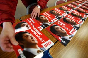 Staff member of Japan's ruling Liberal Democratic Party arranges campaign leaflets showing Japan's Prime Minister Shinzo Abe at the LDP regional election office in Tokyo