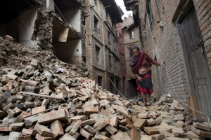 Red Cross handout picture of a woman walking across the rubble of a collapsed building following an earthquake in Bhaktapur