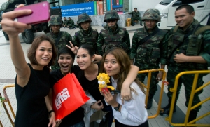 Thai women stop to take a selfie  with Thai soldiers outside Bangkok Art Culture Center in Bangkok ,Thailand Wednesday, May 28, 2014. Thailand's new military junta aired videos Wednesday on television stations nationwide showing some of the prominent political figures it has detained as part of an effort to convince the public that detainees in army custody are being treated well .(AP Photo/Sakchai Lalit)