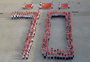 "Students form the figure ""70"" as they pose with Chinese national flags and red stars during a event to mark the 70th anniversary of the Victory of Chinese People's War of Resistance Against Japanese Aggression and the World Anti-Fascist War, at a primary school in Handan, Hebei province, China, August 31, 2015. China will mark the 70th anniversary of the end of World War Two with a massive military parade this Thursday, with some 12,000 soldiers marching through Beijing's central Tiananmen Square. REUTERS/China Daily CHINA OUT. NO COMMERCIAL OR EDITORIAL SALES IN CHINA. TPX IMAGES OF THE DAY - RTX1QCJB"