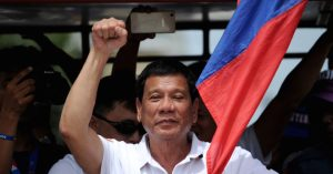 In this photo taken on March 2, 2016, shows Davao City Mayor and Presidential Candidate Rodrigo Duterte raising a clenched fist during his campaign sortie in Lingayen, Pangasinan, north of Manila. Rodrigo Duterte curses the pope's mother and jokes about his own infidelities, but many voters in the Philippines want to elect him president so he can begin an unprecedented war on crime. / AFP / NOEL CELIS / TO GO WITH AFP STORY: Philippines-vote-rights-crime-Duterte, FOCUS by Karl Malakunas        (Photo credit should read NOEL CELIS/AFP/Getty Images)